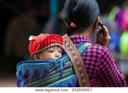 SA PA, VIETNAM - AUGUST 2017: Black hmog ethnic minority woman carrying her child in Sa Pa town, the high mountains, Lao Cai province, Vietnam