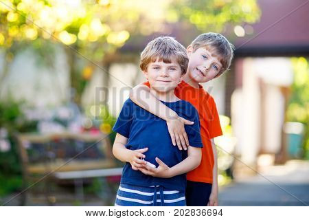 Two little active school kids boys, twins and siblings hugging on summer day. Cute brothers, preschool children and best friends portrait. Family, love, bonding concept.