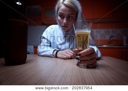 Depressed drunken female sitting at the kitchen and drinking beer. Alcohol addiction.