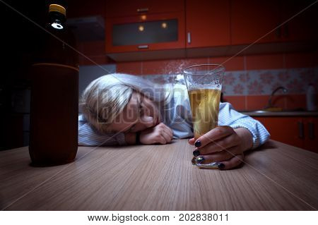 Wide angle shot of young drunken woman with beer bottle and glass lying on the table at home. Alcohol abuse.