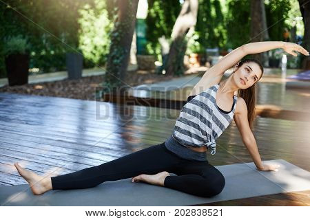 Fit woman stretching in her backyard on a sunny day. Yoga or pilates training. Looking off camera.