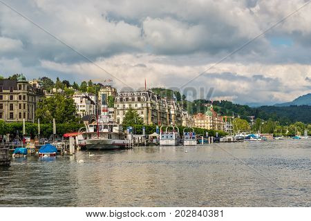Lucerne Switzerland - May 24 2016: Grand Hotel National and buildings along Lake Lucerne people in boats on the lake in cloudy weather. Lucerne is a city in central Switzerland it is the capital of the Swiss Canton of Lucerne.