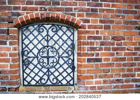 The wall with window of broken and abandoned red brick house. Vintage metal forged lattice is attached to the window. Texture of brick wall with scraps of plaster