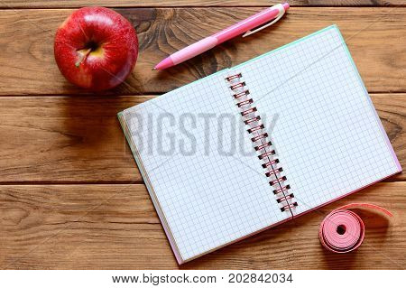 Open notebook for writing notes, pen, apple, measuring tape in centimeters on a wooden table. Workout and dieting diary with copy space for text. Slimming concept