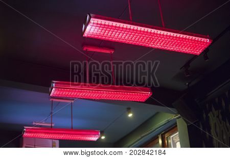 Closeup of hanging red fluorescent ceiling lamp