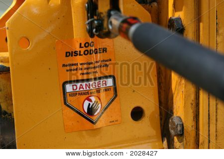 The directional control lever on a log splitter with a warning label for dislodging stuck logs. poster