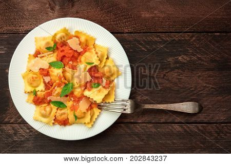 An overhead photo of a plate of ravioli with tomato sauce, with grated Parmesan cheese and basil leaves, shot from above on rustic background with place for text