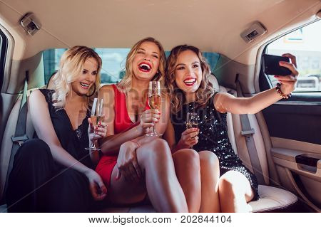 Women drinking champagne and make selfie in a limousine car.