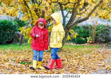 Two little best friends and kids boys autumn park in colorful clothes. Happy siblings children having fun in red and yellow rain coats and rubber boots. Family playing outdoors. active leisure
