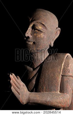 Buddhist monk in serene prayer pose. Holy man in serene meditation pose. Wooden carved statue of monk praying.