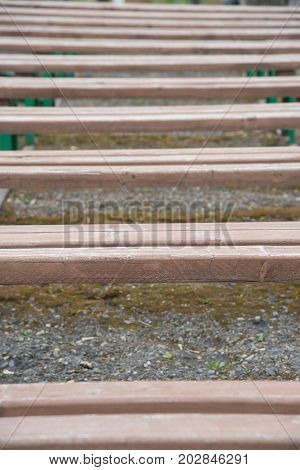 Background of a row of wooden benches without backrest on the street in summer