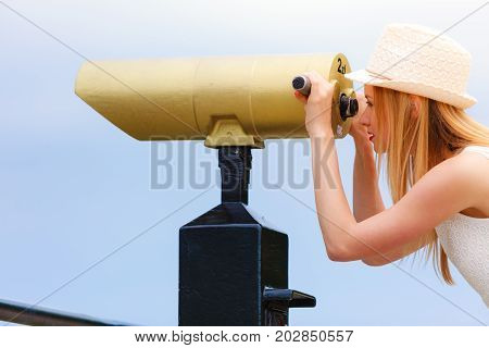Traveling adventure vacation concept. Woman tourist wearing sun hat looking through telescope into the distance