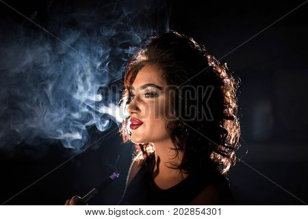Smiled sexy woman on a smoke background. Woman with curly hair and bright make-up