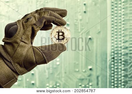 Cryptocurrency physical gold bitcoin coin in man hand on digital mainboard background.