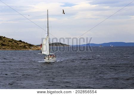 KORNATI NATIONAL NATURE RESERVE, CROATIA - SEPTEMBER 7 2016: This is sailing yacht with tourists-sailors on a walk among the islands of the Kornati archipelago.