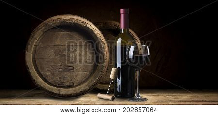 Pouring red wine from bottle into glass with wooden wine casks on background.