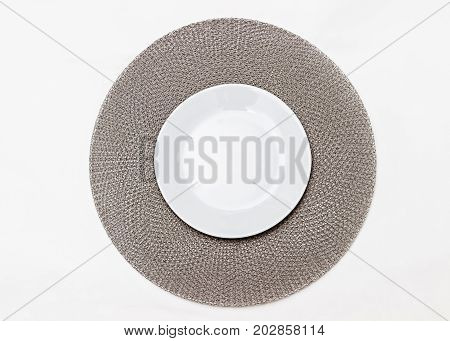 Empty plate on a gray napkin. White saucer. Plateful on a knitted napkin.