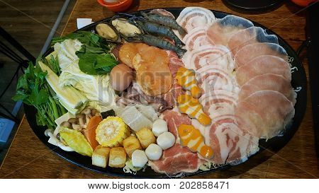 Mixed ingredients on a serving plat including sliced pork , seafood and vegetable for Shabu party.