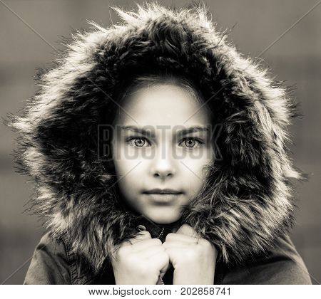 black and white image showing a girl with a pretty face looking proud out of a hood with fur