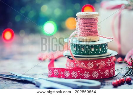 Christmas decoration with vintage ribbon spools for homemade gift boxes on christmas lighting bokeh background