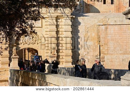 MDINA, MALTA - MARCH 29, 2017 - Horse and carriage and tourists crossing the town gate footbridge Mdina Malta Europe, March 29, 2017.