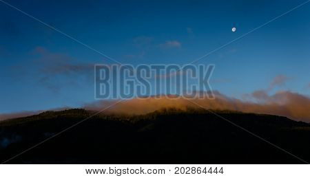 mountain glowing over the orange lid clouds on the mountain
