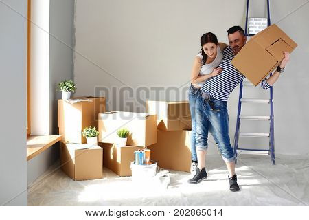 Happy young couple unpacking or packing boxes and moving into a new home. young couple