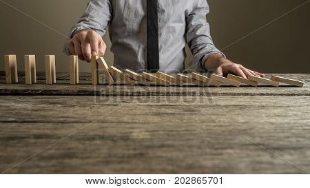 Front View Of A Businessman Stopping Domino Effect With His Finger