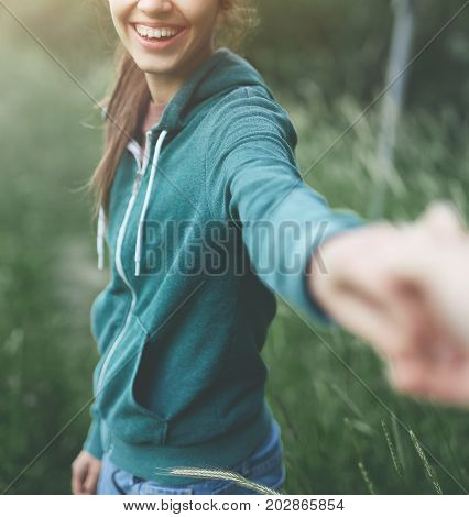 Young girl wering in hoody outstretching hand asking to follow her on background of green field. focus on the woman's hand