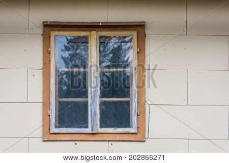 AN old window in an old white wall