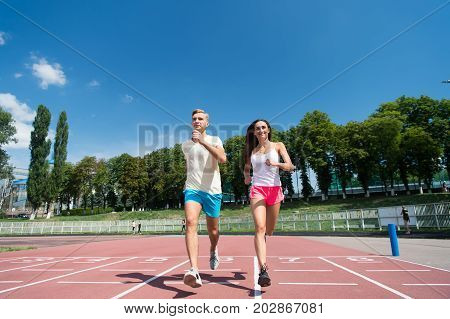 Couple running on arena track. Sport and healthy fitness. Man and woman sunny outdoor on blue sky. Coach and trainer at workout. Runner on competition and future success.