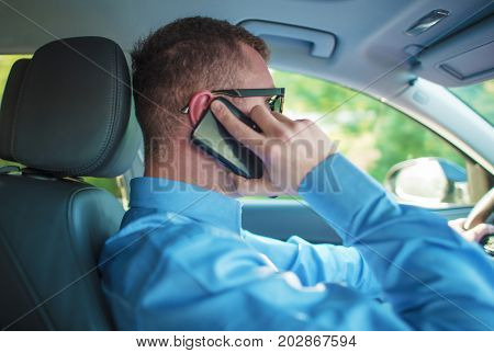 Talking by Phone While Driving. Caucasian Men Making Conversation While Driving the Car.