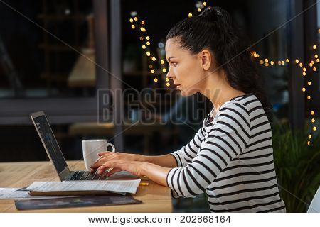 Work addiction. Serious smart hard working woman sitting at the laptop and typing while being concentrated on her work