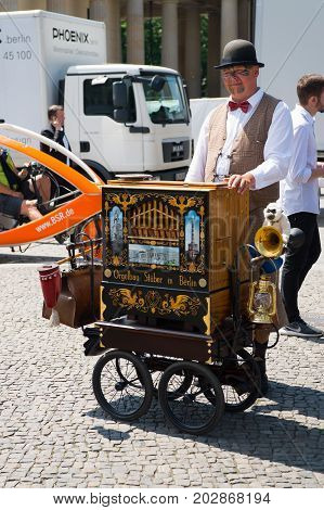 Berlin Germany - May 31 2017: man with barrel organ in city on sunny day. Street music and entertainment concept. Summer vacation and lifestyle