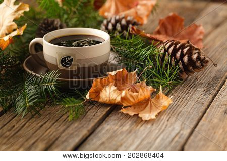 Hot coffee and pine coneson on table wood background with copy space.