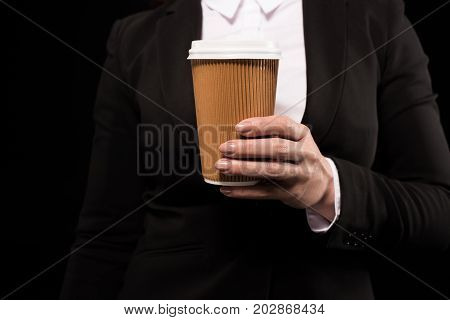 Cropped shot of a woman in a suit holding a disposable coffee cup in her hand