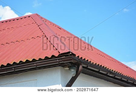 Close up on red roofing construction house with roof gutter system.