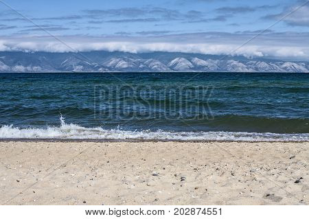Blue waves of Lake Baikal in Siberia in the summer are broken against a sandy beach on a mountain and sky background in a clear sunny day.