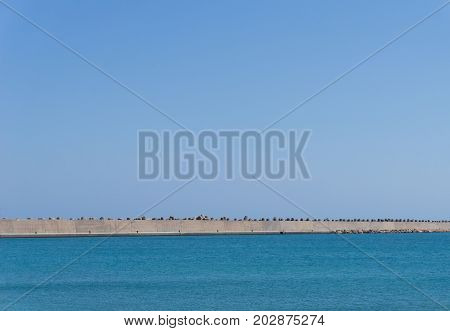 View on a large Stona Wall in front of a blue Sea. Close-up of a Dam in front of blue Water. Nature Background.
