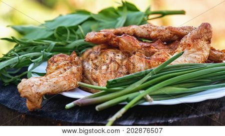 Chicken grilled with herbs on a wooden stand. Selective focus. The horizontal frame.