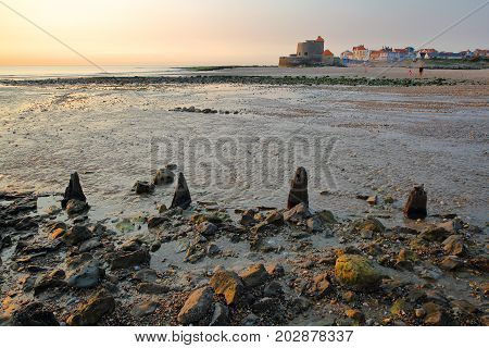 The beach of Ambleteuse at sunset with colorful stones in the foreground and the fort in the background, Cote d'Opale, Pas de Calais, Hauts de France