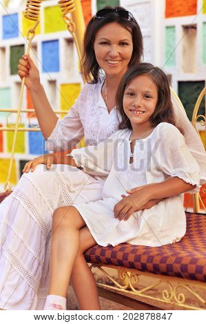 Mother and daughter sitting on soft swing and looking at camera