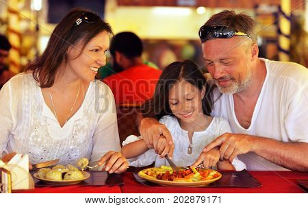 Smiling parents teaching their daughter to use knife in cafe