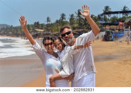 Portrait of a happy family wawing hands on seashore