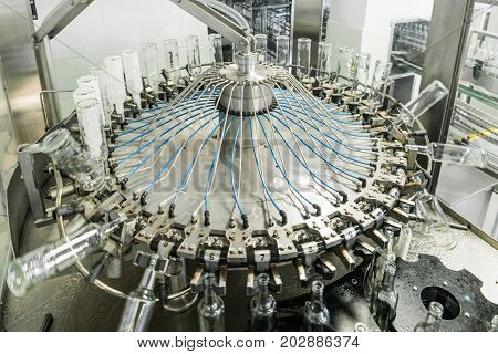 The machine for washing glass bottles. Factory for bottling alcoholic beverages.