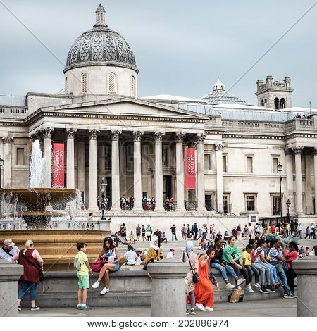 LONDON UK - 29 AUGUST 2017: Tourists sitting around a fountain in the popular Trafalgar Square with the National Gallery in the background.