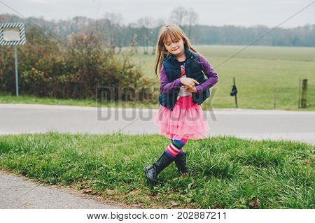 Outdoor portrait of little 5 year old girl in autumn wearing pink tutu skirt