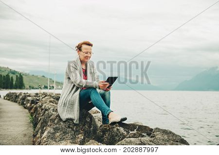 Middle age woman resting by the lake using tablet pc outdoors