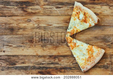 Two piece of fresh pizza four cheese on a wooden table top view
