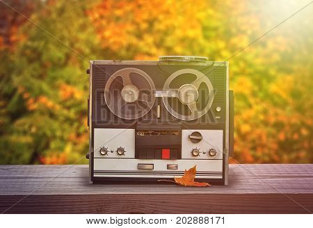 Old reel tape recorder standing on wooden table autumn background retro